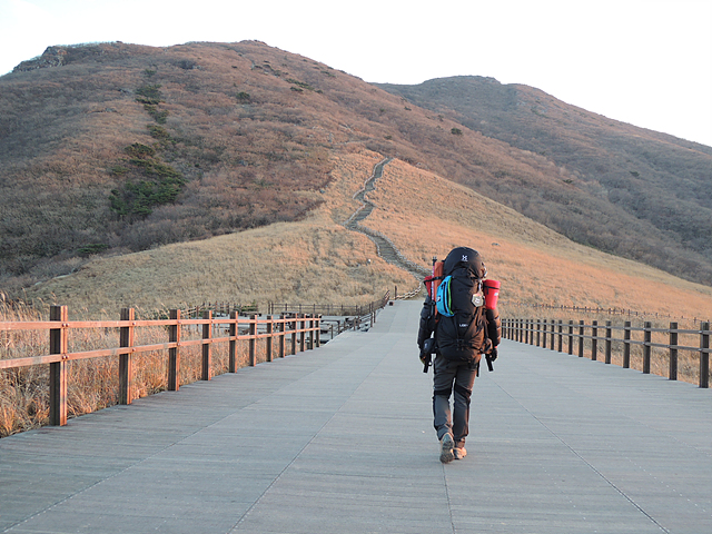가방은 메고 산에 올라가는 모습