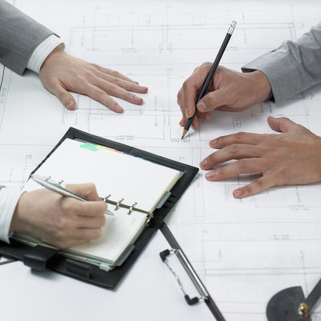 설계 도면을 가운데 두고 두 사람이 논의를 하고 있다.