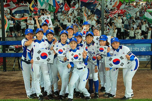 한국 여자야구 대표팀 선수들이 태극기를 들고 서 있는 모습