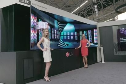 -: LG전자 모델이 사용자가 원하는 형태로 휘어짐을 조절할 수 있는 'LG 플렉서블 올레드 사이니지'를 소개하고 있다.
