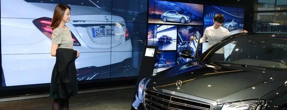LG전자가 지난달 문을 연 메르세데스-벤츠 청담 전시장에 비디오월 등 총 55대의 LCD 사이니지를 설치했다. 모델들이 LCD 사이니지(모델명: 55VH7B) 18대를 이어 붙인 대형 비디오월 앞에서 차량을 살펴보고 있다.