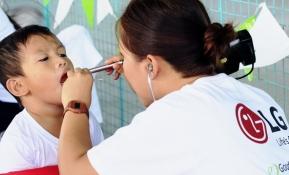 LG전자가 의료시설이 낙후된 동남아 지역의 건강 증진에 앞장서며 기업의 사회적 책임을 적극 실천한다. LG전자는 20일 필리핀 산토 로사리오에 위치한 하고노이중서부학교에 이동진료소를 열고, 200여 명의 주민들을 무료로 진료했다. LG전자는 올해 4월부터 필리핀 캄보디아 등에서 이동진료소를 운영하고 있다. 올해 약 2만 명의 주민들이 진료를 받았고, 연말까지 모두 4만 명이 무료 진료 혜택을 받을 것으로 예상된다. 20일 필리핀 하고노이중서부학교에서 의료진이 지역 어린이를 검진하고 있다.