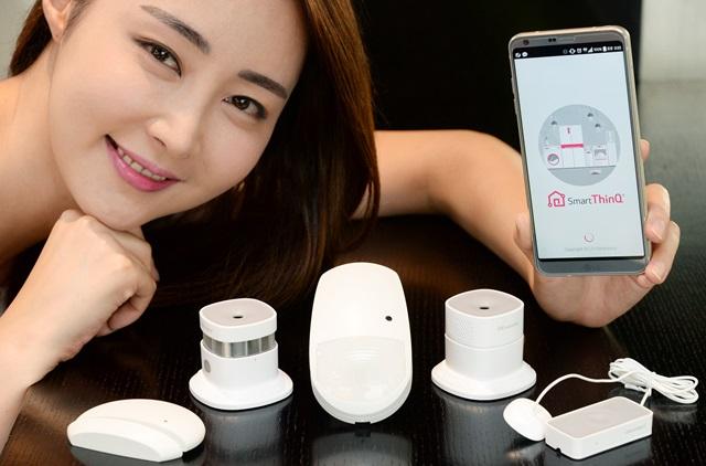 모델이 LG전자 스마트홈 어플리케이션인 '스마트씽큐'와 연동하는 IoT 센서 5종을 소개하고 있다. 왼쪽부터 열림감지 센서, 연기 센서, 모션 센서, 일산화탄소 센서, 누수 센서.