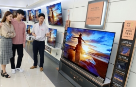 : 'LG 올레드 TV'가 국내에서 월판매량 1만대를 넘어서며 대중화 속도를 높이고 있다. 이는 4분마다 한 대꼴로 팔려나간 셈으로, 올해 초와 비교해 2배로 늘었다. LG전자는 뛰어난 화질과 합리적인 가격 덕분에 판매량이 늘어난 것으로 보고있다. LG전자 모델들이 가전 매장에서 'LG 올레드 TV'를 살펴보고 있다.
