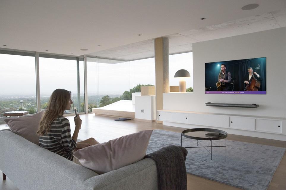 고객이 LG 올레드 TV 의 음성인식 기능을 활용해 콘텐츠를 검색하고 있다.