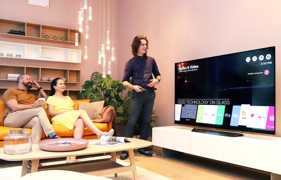 뉴욕 맨해튼 '보컨셉' 플래그십 쇼룸을 방문한 고객들이 LG 올레드 TV와 보컨셉 가구, 소품들로 연출한 거실 공간에서 대화를 나누고 있다.