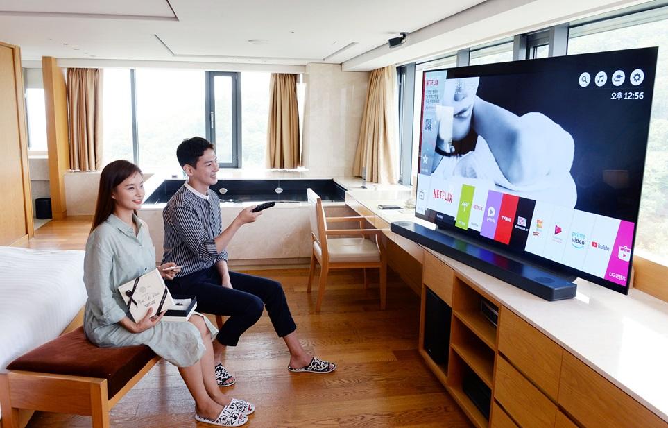 서울 남산에 위치한 '반얀트리 클럽 앤 스파 서울' 객실에서 모델들이 스파를 즐기면서 LG 올레드 TV와 사운드바가 구현하는 압도적 화질과 생생한 사운드를 감상하고 있다.