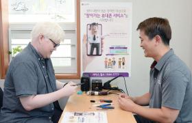 17일 백색증과 저시력 장애로 외출이 불편한 장애인이 LG전자 '찾아가는 휴대폰 서비스'를 신청해 서울 강남구에 위치한 하상복지관에서 스마트폰 수리를 받고 있다. LG전자는 거동이 불편한 장애인들이 스마트폰 때문에 서비스 센터를 방문하는 번거로움을 줄여주는 '찾아가는 휴대폰 서비스'를 시작했다. 콜센터(1544-7777)에 '찾아가는 휴대폰 서비스'를 신청하고 방문 날짜와 시간을 정하기만 하면 된다. 보증기간 내 제품 하자의 경우, 서비스 요금은 물론 출장비도 무료다.