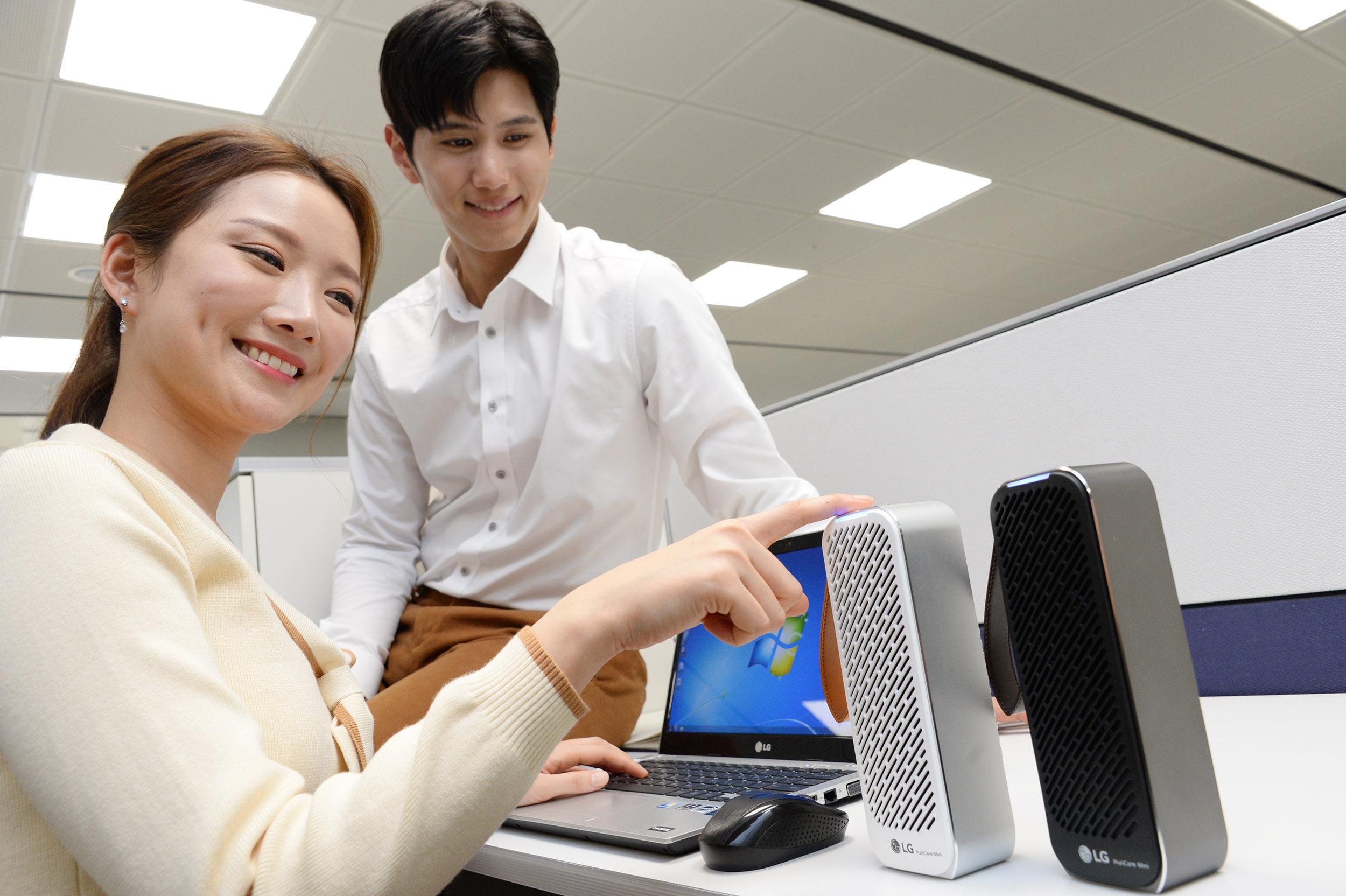 LG전자가 22일 휴대용 공기청정기 'LG 퓨리케어 미니 공기청정기'를 출시한다. 사진은 모델이 사무실에서 LG 퓨리케어 미니 공기청정기를 가리키는 모습