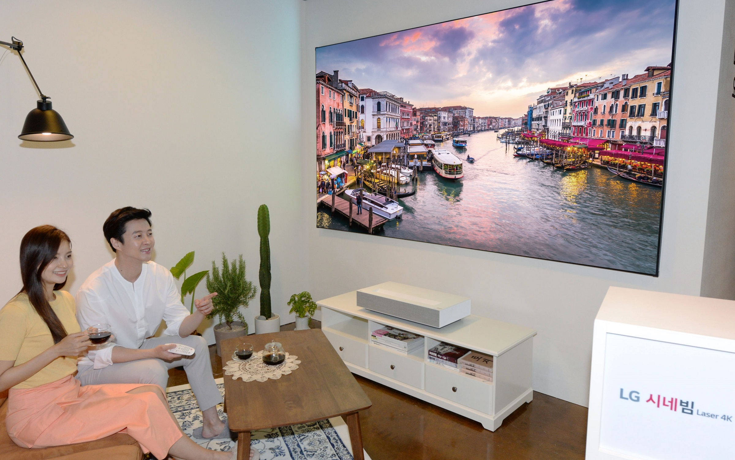 모델들이 스크린과 10cm 거리서 100인치 초대형 화면 구현이 가능한 'LG 시네빔 Laser 4K' 프로젝터(모델명:HU85LA)를 이용해 4K 초고화질 화면을 즐기고 있다.