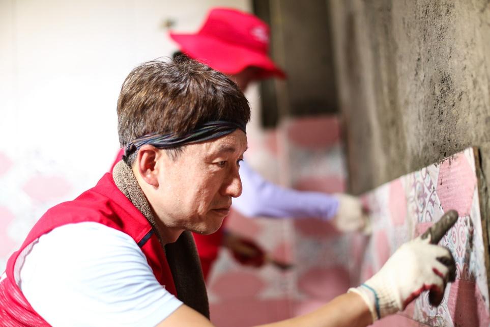 샤워실 건물 내벽에 타일을 붙이는 LG전자 직원