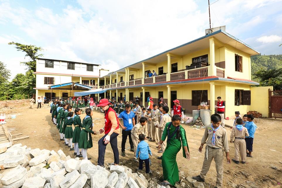 학교 운동장에 블록 설치를 하는 LG전자 해외임직원 봉사단과 학생들