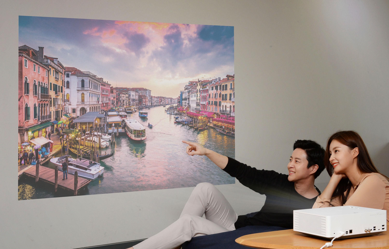 서울 여의도 LG트윈타워에서 모델들이 'LG 시네빔 4K' 프로젝터가 구현하는 초대형 화면으로 영상을 즐기고 있다.
