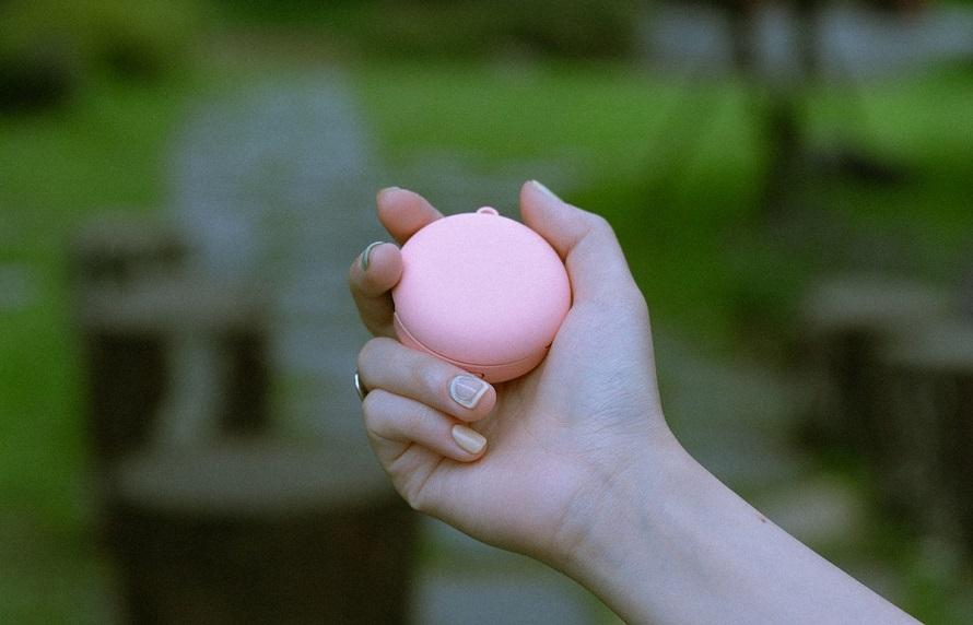 핑크 케이스를 끼운 LG 톤 프리를 손으로 잡고 있는 모습