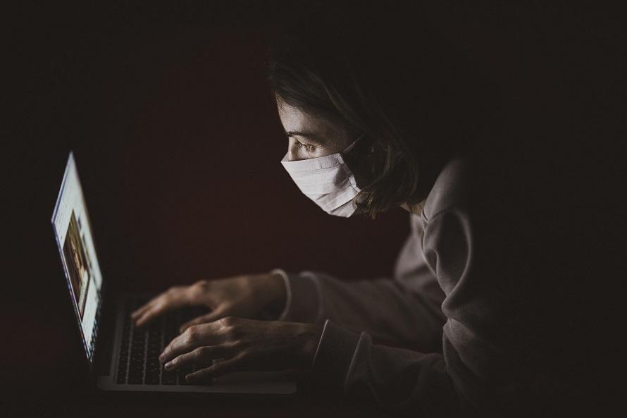 마스크 쓴 여성이 노트북을 들여다보는 모습