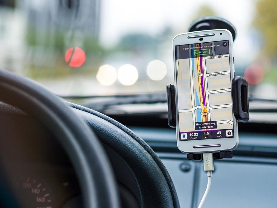 자동차 모바일 거치대에 끼워진 스마트폰으로 내비게이션을 켠 모습