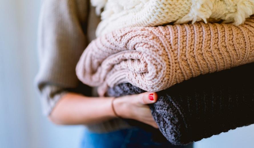 잘 개어진 스웨터를 들고 옮기는 모습