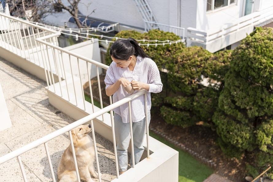 야외 복도에서 난간에 몸을 기댄 채 옆에 앉은 강아지를 내려다보고 있는 여성의 모습