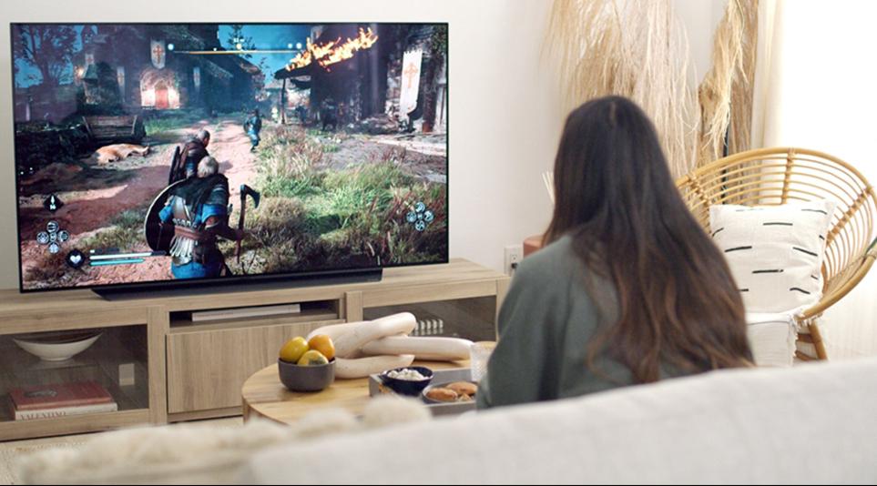 LG 올레드 TV로 거실에서 게임을 즐기고 있는 소비자의 모습