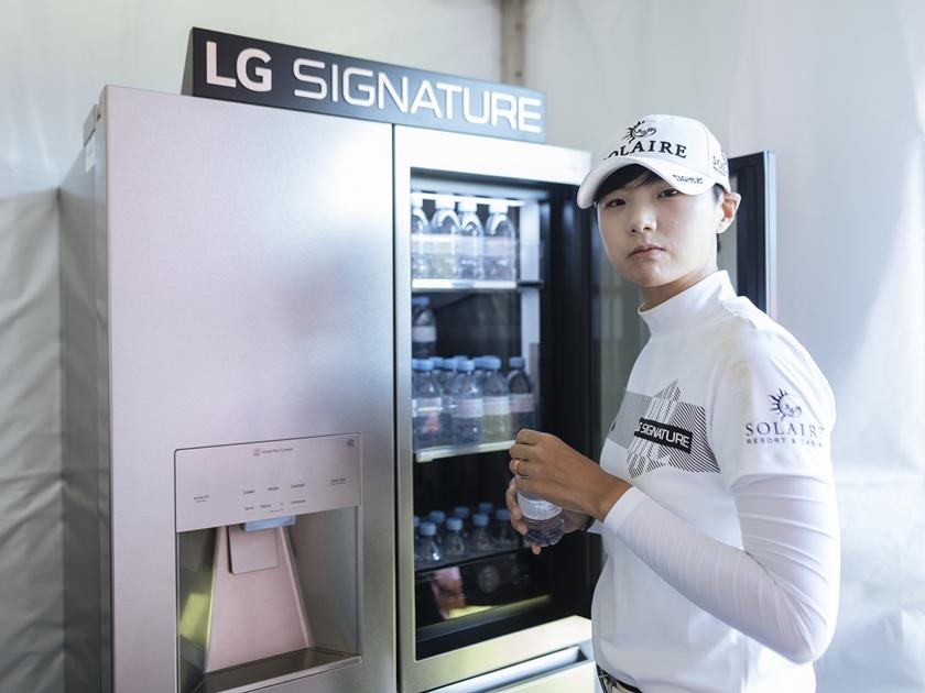 1번홀 내 LG 시그니처 체험존에서 박성현 선수가 냉장고 안의 에비앙 생수를 꺼내 마시며 직접 제품을  체험해보고 있다.