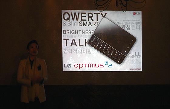 LG전자 허자영 매니저가 나와 옵티머스 Q2에 대해 소개하고 있으며 화면으로 옵티머스 Q2의 제품 사진을 보여주고 있다.