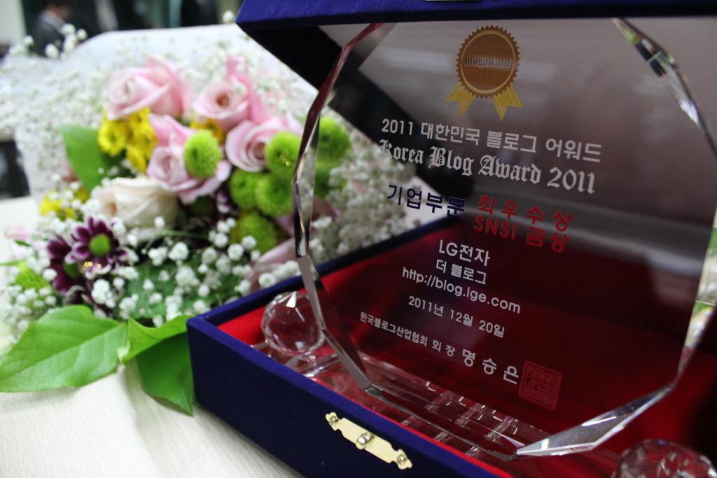 기업블로그 부문에서 최우수상과 SNS금상을 수상해 받은 상패의 모습과 꽃이 보인다.